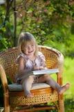 Libro di lettura della bambina in presidenza di vimini esterna Immagine Stock Libera da Diritti