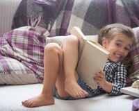 Libro di lettura della bambina sul sofà Fotografie Stock Libere da Diritti