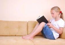 Libro di lettura della bambina sul sofà Fotografia Stock