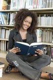 Libro di lettura della donna alla biblioteca Fotografie Stock Libere da Diritti