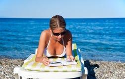 Libro di lettura della donna alla spiaggia Immagine Stock