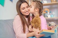 Libro di lettura della donna della figlia e della madre insieme a casa alla ragazza immagini stock libere da diritti