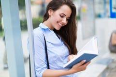 Libro di lettura della donna mentre aspettando bus Fotografie Stock Libere da Diritti