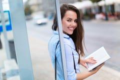 Libro di lettura della donna mentre aspettando bus Fotografia Stock