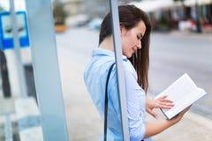 Libro di lettura della donna mentre aspettando bus Immagini Stock