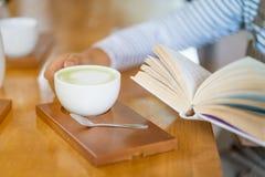 Libro di lettura della donna mentre bevendo caffè Fotografia Stock Libera da Diritti