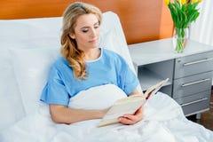 Libro di lettura della donna nel letto di ospedale Fotografia Stock
