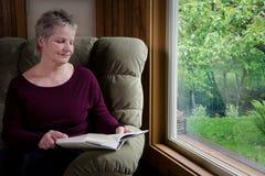 Libro di lettura della donna più anziana dalla finestra Immagini Stock