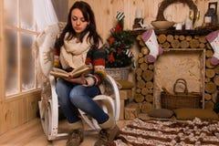 Libro di lettura della donna in sedia in cabina rustica Immagini Stock
