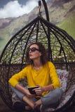 Libro di lettura della donna sul dispositivo digitale Goda della vacanza Ragazza dei pantaloni a vita bassa che si rilassa le gam Fotografie Stock