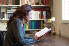 Libro di lettura della donna sulla tavola di legno Fotografie Stock