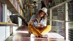 Libro di lettura della donna vicino agli scaffali per libri in biblioteca archivi video