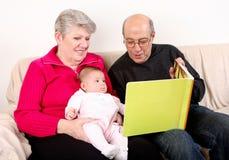 Libro di lettura della famiglia al bambino Fotografia Stock Libera da Diritti