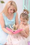 Libro di lettura della figlia e della madre immagine stock