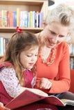 Libro di lettura della figlia e della madre in biblioteca Fotografia Stock