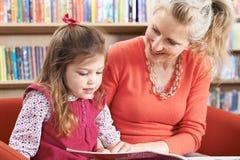 Libro di lettura della figlia e della madre in biblioteca Fotografie Stock