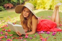 Libro di lettura della giovane donna all'esterno Fotografie Stock