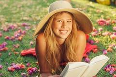 Libro di lettura della giovane donna all'esterno Immagine Stock Libera da Diritti