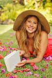 Libro di lettura della giovane donna all'esterno Immagini Stock