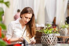 Libro di lettura della giovane donna alla tavola in caffè fotografie stock libere da diritti