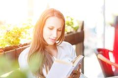 Libro di lettura della giovane donna alla tavola in caffè fotografia stock libera da diritti