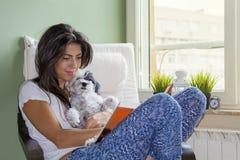 Libro di lettura della giovane donna con il suo cane in un parco di autunno Immagine Stock