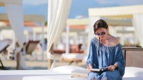 Libro di lettura della giovane donna durante la vacanza tropicale della spiaggia La ragazza di modo ha letto la seduta nei lettin video d archivio
