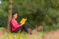 Libro di lettura della giovane donna nel parco Fotografia Stock Libera da Diritti