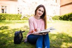 Libro di lettura della giovane donna in parco il giorno soleggiato dell'erba fotografia stock libera da diritti