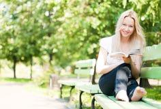 Libro di lettura della giovane donna in sosta Fotografia Stock