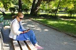 Libro di lettura della giovane donna sul libro-lettore elettronico Fotografia Stock