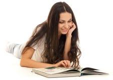 Libro di lettura della giovane donna sul pavimento isolato Immagine Stock