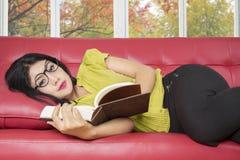 Libro di lettura della giovane donna sul sofà Immagine Stock Libera da Diritti