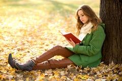 Libro di lettura della ragazza all'aperto Fotografie Stock