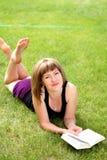 Libro di lettura della ragazza all'aperto Fotografia Stock