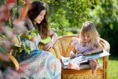 Libro di lettura della ragazza che si siede nelle presidenze di vimini esterne Fotografia Stock