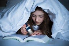 Libro di lettura della ragazza con la torcia elettrica Fotografie Stock