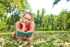 Libro di lettura della ragazza dell'allievo esterno Fotografie Stock Libere da Diritti