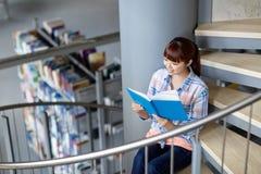Libro di lettura della ragazza dello studente della High School alla biblioteca Immagini Stock Libere da Diritti