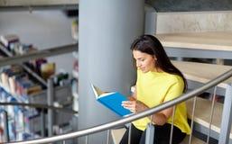 Libro di lettura della ragazza dello studente della High School alla biblioteca Immagine Stock