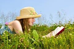 Libro di lettura della ragazza in prato Fotografia Stock Libera da Diritti