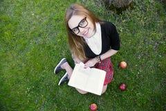 Libro di lettura della ragazza/studente che legge un libro in parco/ Immagini Stock