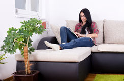 Libro di lettura della ragazza sul sofà Fotografia Stock