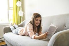 Libro di lettura della ragazza sulla casa di Sofa In Living Room At immagine stock libera da diritti