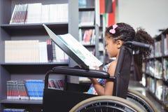 Libro di lettura della ragazza sulla sedia a rotelle Immagine Stock