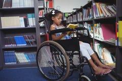 Libro di lettura della ragazza sulla sedia a rotelle in biblioteca Fotografie Stock Libere da Diritti