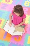 Libro di lettura della ragazza sulla stuoia del pavimento di alfabeto Immagini Stock Libere da Diritti