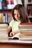 Libro di lettura della scolara con la pila di libri a Immagini Stock Libere da Diritti