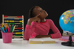 Libro di lettura della scolara contro fondo nero Fotografia Stock