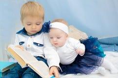 Libro di lettura della sorella e del fratello fotografia stock libera da diritti